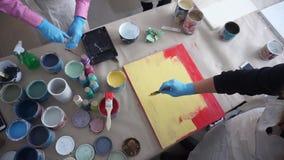 De kunstenaar schildert een houten raad Rode en Gele Verf Art Studio Verfblikken en borstels stock footage