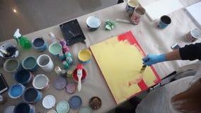 De kunstenaar schildert een houten raad Rode en Gele Verf Art Studio Verfblikken en borstels stock video