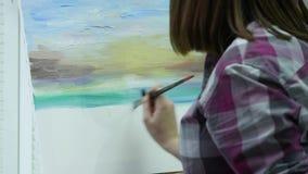 De kunstenaar schildert een vrouw op canvas en smeert een brede borstel Canvastribunes op de schildersezel De kunstenaar trekt bi stock video