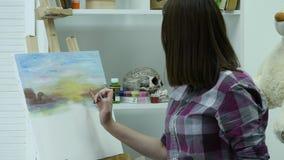 De kunstenaar schildert een vrouw op canvas en smeert een brede borstel Canvastribunes op de schildersezel De kunstenaar trekt bi stock videobeelden
