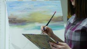 De kunstenaar schildert een vrouw op canvas en smeert een brede borstel Canvastribunes op de schildersezel De kunstenaar trekt bi stock footage