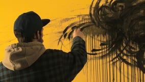 De kunstenaar schildert het abstracte ornament met zwarte borstel op gele muur stock videobeelden