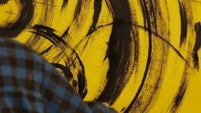 De kunstenaar schildert het abstracte ornament met zwarte borstel op gele muur stock footage