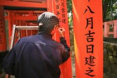 De kunstenaar schrijft geschonken naam op toriipoorten Stock Foto's