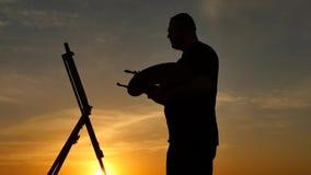 De kunstenaar schrijft in openlucht een beeldsilhouet bij zonsondergang stock footage