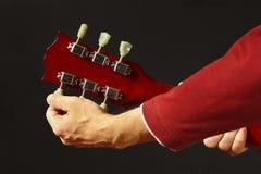 De kunstenaar stemt de gitaar op donkere achtergrond royalty-vrije stock afbeelding