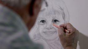 De kunstenaar trekt een klein die meisje op canvas achter zijn rug wordt geschoten stock video