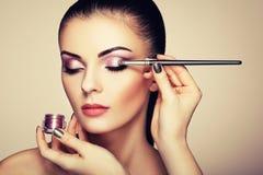 De kunstenaar van de make-up past oogschaduw toe royalty-vrije stock foto's