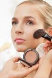 De kunstenaar van de make-up schrijft bloost op wangen in stock afbeelding