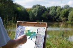 De kunstenaar van de schildersezel in aard. Trek landschap van aard Royalty-vrije Stock Foto's