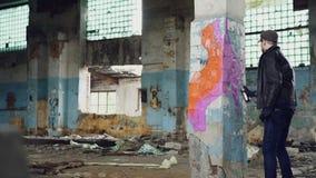 De kunstenaar van de jonge mensengraffiti schildert op pijler in de oude vuile bouw met de verf van het nevelaërosol De ruwe kere stock footage