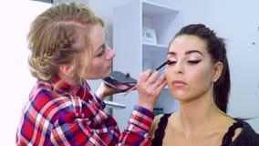 De kunstenaar van de make-up op het werk Make-upmodel stock videobeelden