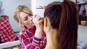 De kunstenaar van de make-up op het werk Make-upmodel stock video