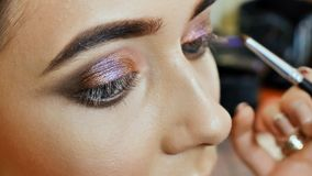 De kunstenaar van de meisjesmake-up schildert de ogen van het meisjesmodel Slag van hogere oogleden Royalty-vrije Stock Afbeeldingen