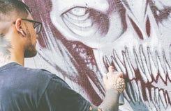 De kunstenaar van de straatgraffiti het schilderen met een kleur bespuit een donkere graffiti van de monsterschedel op de Stedeli stock foto's