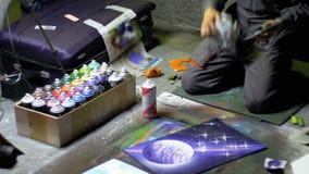 De kunstenaar van de straatgraffiti schildert een beeld gebruikend nevelverf bij nacht stock footage