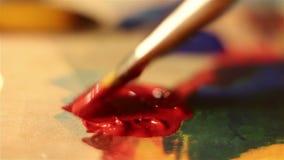 De kunstenaar vermindert de borstel in rode verf en mengt het op het palet stock video