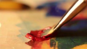 De kunstenaar vermindert de borstel in rode verf en mengt het op het palet stock videobeelden
