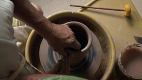 De kunstenaar werkt met klei bij kunststudio en creeert een waterkruik stock videobeelden