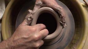 De kunstenaar werkt met klei bij kunststudio en creeert een waterkruik stock footage