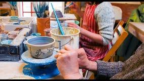 De kunstenaars die op aardewerk trekken werpen stock video