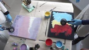 De kunstenaars drogen abstracte schilderijen met droogkappen Art Studio Verfblikken en borstels Hoogste mening stock videobeelden