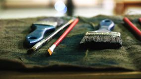 De kunstenaars` s borstels liggen op de lijst, die hulpmiddelen van de kunstenaar werken stock videobeelden