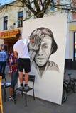 De kunstenaars schilderen een portret van een militair op Victory Day-viering Stock Afbeelding