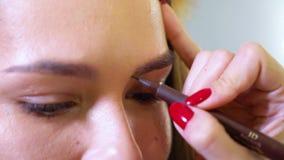 De kunstenaarshand die van de close-up vrouwelijke make-up de correctie van de wenkbrauwvorm doen aan vrouwelijk model bij schoon stock video