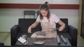 De kunstenaarsvrouw verpakt ceramische plaat in ambachtdocument, aanhalend door kabel stock footage