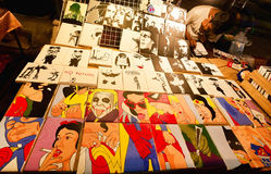 De kunsthandelaar van nachtmarkt verkoopt vele kleurrijke pop-artbeelden met film en beeldverhaalhelden Stock Fotografie