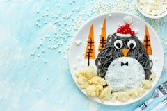 De kunstidee van het pretvoedsel voor jonge geitjes - pinguïn zwarte spagehetti met gebraden Stock Afbeeldingen