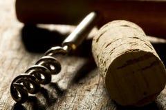 De kurketrekker met houten handvat en kurkt van wijnflessen op hout Royalty-vrije Stock Foto's