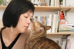 De kus van de kat haar meester Stock Afbeeldingen