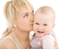 De kus van de moeder haar babymeisje stock afbeelding