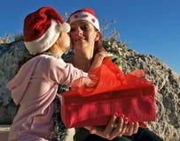 De kusmoeder van het meisje met de gift van Kerstmis Stock Fotografie