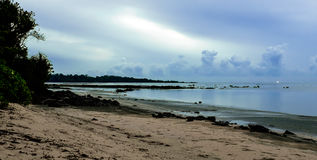 De kust bij schemer De wolken van Nice boven zandig en steenstrand Stock Foto's