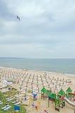 De kust, de kust van de Zwarte Zee met gouden zand, sunbeds, blauwe hemel, duidelijk water, paraplu's en groene vegetatie Stock Afbeelding