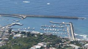 De kust met kleine haven en de gedokte boten scheidden van veranderlijke overzees door golfbreker stock videobeelden