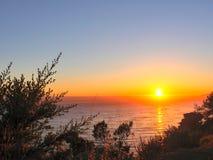 De kust oceaanzonsondergang van Californië met lichte golven op de oceaanoppervlakte stock afbeeldingen