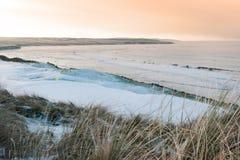 De kust sneeuw behandelde links golfcursus bij zonsondergang royalty-vrije stock foto