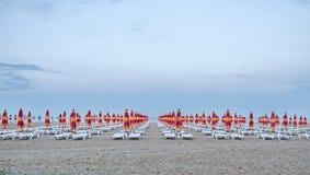 De kust van de Zwarte Zee blauw zeewater, de hemel van de wolkenzonsondergang, strandzand met paraplu's en sunbeds Stock Foto's