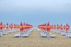 De kust van de Zwarte Zee blauw zeewater, de hemel van de wolkenzonsondergang, strandzand met paraplu's en sunbeds Stock Fotografie