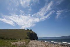 De kust van het blauwe meer en de heldere hemel met cirrus betrekt royalty-vrije stock foto