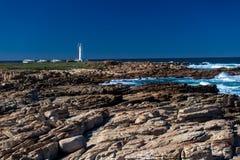 De kustlijn schommelt Witte Vuurtoren Stock Foto's