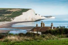 De Kustwacht Cottages & Zeven ZustersKrijtrotsen enkel buiten Eastbourne Stock Foto
