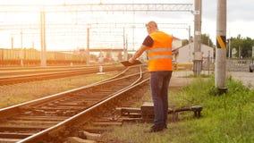 De kwade leider op de spoorweg inspecteert het mechanisme van de schakelaarspoorweg en gilt op de telefoon royalty-vrije stock foto