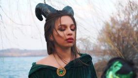 De kwade magische koningin creeert betovering tegen vijand, slaat de zwarte heks in lange groene smaragdgroene kledingsmantel mag stock footage