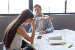 De kwade werkgever in het bureau richt de jonge meisjes` s vinger op de uitgang stock afbeeldingen
