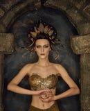 De kwallen van het meisjeskostuum gorgon met gouden bustehouder van schalen in een steenboog stock foto